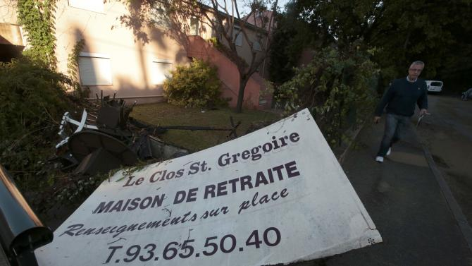 A damaged sign is seen outside the retirement home where three people died after flooding caused by torrential rain in Biot