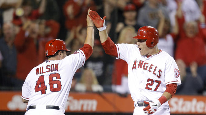 Los Angeles Angels' Mike Trout, right, and teammate Bobby Wilson high-five after they scored on a single hit by Torii Hunter in the sixth inning of a baseball game in Anaheim, Calif., Friday, June 22, 2012. (AP Photo/Jae C. Hong)