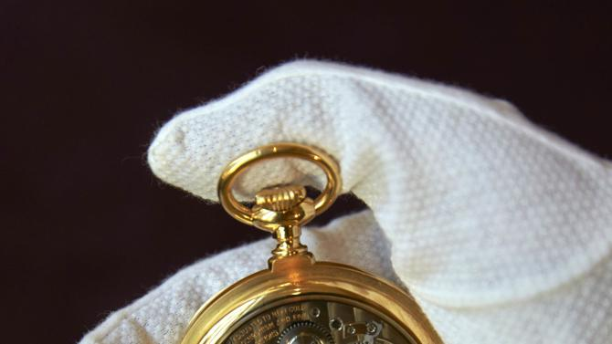 A Sotheby's staff holds a pocket golden watch by Patek Philippe during an auction preview in Geneva