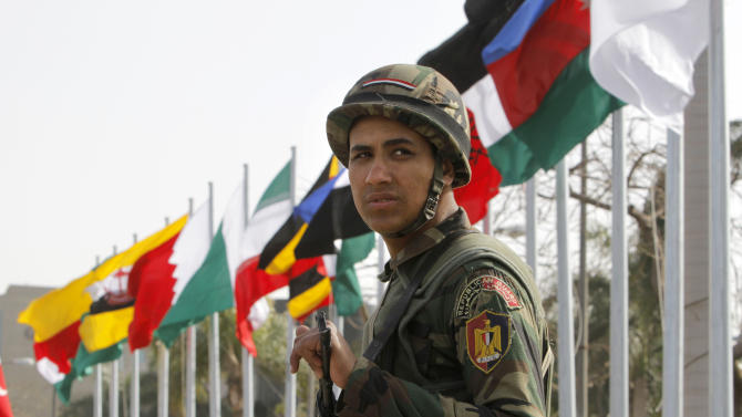 An Egyptian presidential guard soldier stands in front of flags of participating countries at the 12th summit of the Organization of Islamic Cooperation in Cairo, Egypt, Wednesday, Feb. 6, 2013.  The summit aims to address a wide range of issues including, Palestinian statehood, the Syrian crisis, poverty in the Islamic world and conflicts in Afghanistan and Somalia. (AP Photo/Amr Nabil)