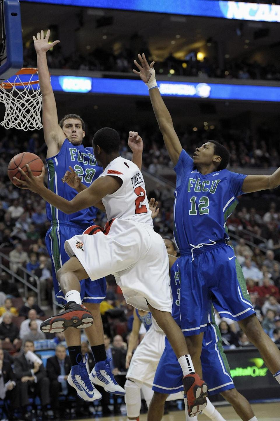 San Diego State's Xavier Thames (2) tries to get a past around Florida Gulf Coast's Chase Fieler (20) and Eric McKnight (12) during the first half of a third-round game of the NCAA college basketball tournament, Sunday, March 24, 2013, in Philadelphia. (AP Photo/Michael Perez)