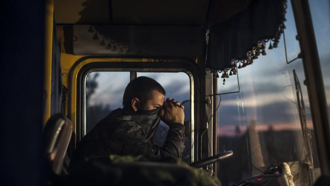 A driver sits inside a bus during an exchange of prisoners-of-war (POWs) near Donetsk, eastern Ukraine
