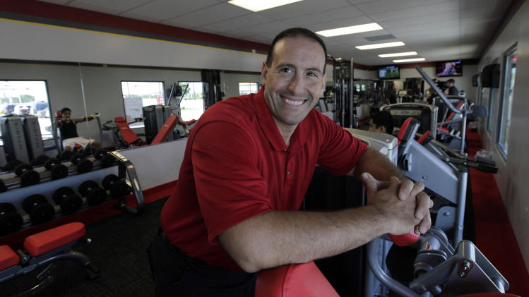 In this June 14, 2012, photo, Rick Limitone, manager of Snap Fitness, posses for a photo at the truck stop gym in Dallas. From trucking companies embracing wellness and weight-loss programs to gyms being installed at truck stops, momentum has picked up in recent years to help those who make their living driving big rigs get into shape. (AP Photo/LM Otero)