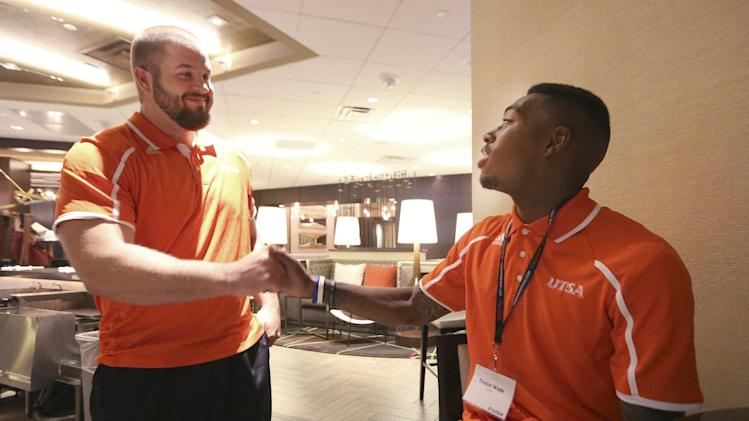 UTSA guard Scott Inskeep, left, shakes hands with teammate safety Tristan Wade as they talk about the 38 returning seniors that will play on their team this season during the NCAA college Conference USA football media day in Irving, Texas Wednesday, July 23, 2014. (AP Photo)