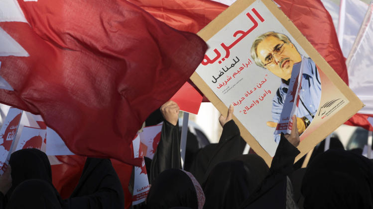 "Bahraini anti-government protesters wave national flags and carry signs during a march called by several opposition groups to demand freedom for political prisoners and democracy, in Muharraq, Bahrain, on Monday Feb. 4, 2013. Arabic on poster showing a jailed opposition leader reads, ""Freedom for Ibrahim Sherief,"" (AP Photo/Hasan amali)"