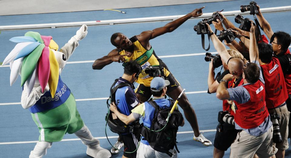 Jamaica's Usain Bolt, center, poses for photographers as he celebrates winning the Men's 200m final at the World Athletics Championships in Daegu, South Korea, Saturday, Sept. 3, 2011. (AP Photo/Kevin Frayer)