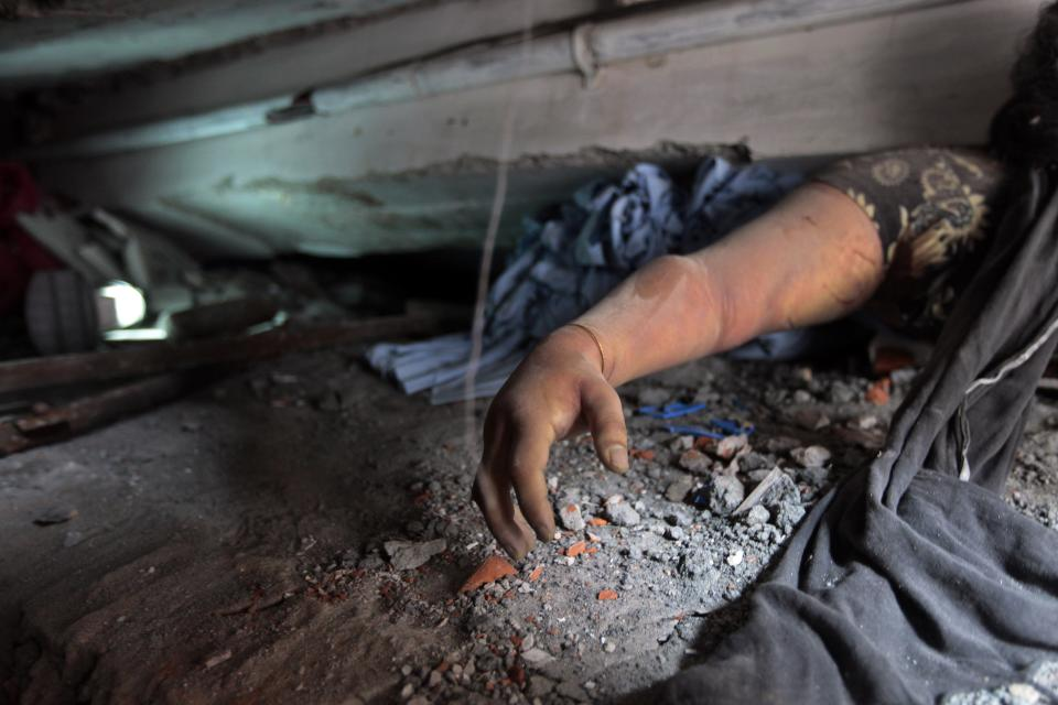 A victim's body is trapped in rubble after an eight-story building housing several garment factories collapsed in Savar, near Dhaka, Bangladesh, Wednesday, April 24, 2013. Dozens were killed and many more are feared trapped in the rubble. (AP Photo/A.M. Ahad)
