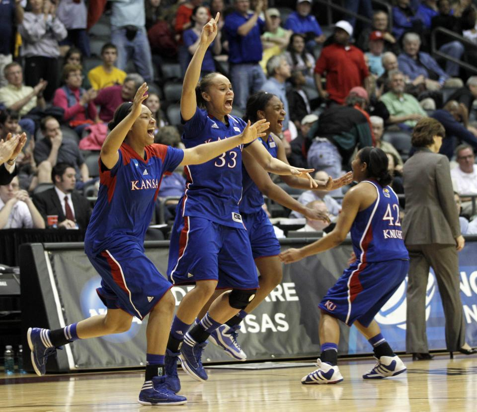 Kansas' Tania Jackson (33), Natalie Knight (42), and other team members celebrate their 70-64 victory over Delaware in an NCAA tournament second-round women's college basketball game in Little Rock, Ark., Tuesday, March 20, 2012. (AP Photo/Danny Johnston)