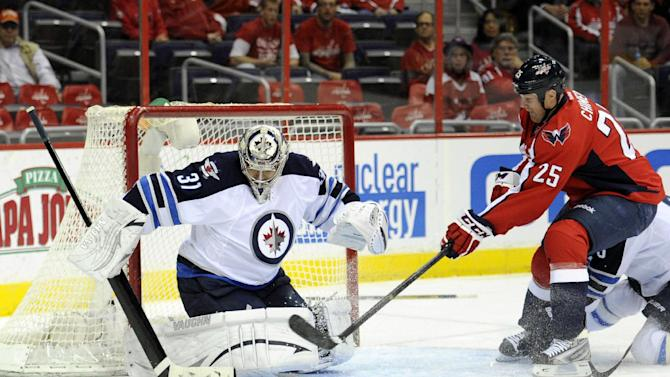 Winnipeg Jets goalie Ondrej Pavelec (31), of the Czech Republic, tracks the puck against Washington Capitals left wing Jason Chimera (25) during the first period of an NHL hockey game, Tuesday, April 23, 2013, in Washington. (AP Photo/Nick Wass)