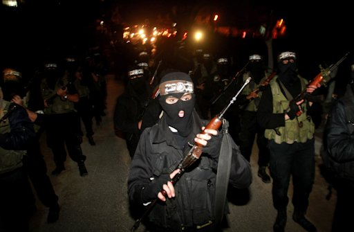 Masked Hamas militants march with their guns during a parade to mark the third anniversary of the Israeli offensive on Gaza in 2008, in Gaza City, Tuesday, Dec. 27, 2011. Palestinians mark the third anniversary of the three-week offensive Israel launched in Gaza in late 2008.  (AP Photo/Hatem Moussa)