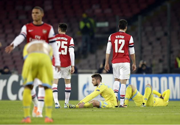 Players leave the field at the end of a Champions League, group F soccer match, at the Naples San Paolo stadium, Italy, Wednesday, Dec. 11, 2013. Ten-man Arsenal advanced to the Champions League knock