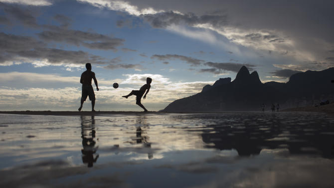 """FILE -  In this Dec. 16, 2011 file photo, two men play soccer at Ipanema beach in Rio de Janeiro, Brazil. The bossa nova song, """"The Girl From Ipanema"""" is turning 50, and to its legions of fans, the decades have only heightened its allure. The tune inspired by a young woman who passed the songwriters in a beach side bar on her way to the waters of Ipanema beach, carries within its chords and lyrics an image of a city that's light and easy, palm trees and blue sky, a sun-kissed life without care. (AP Photo/Felipe Dana, File)"""