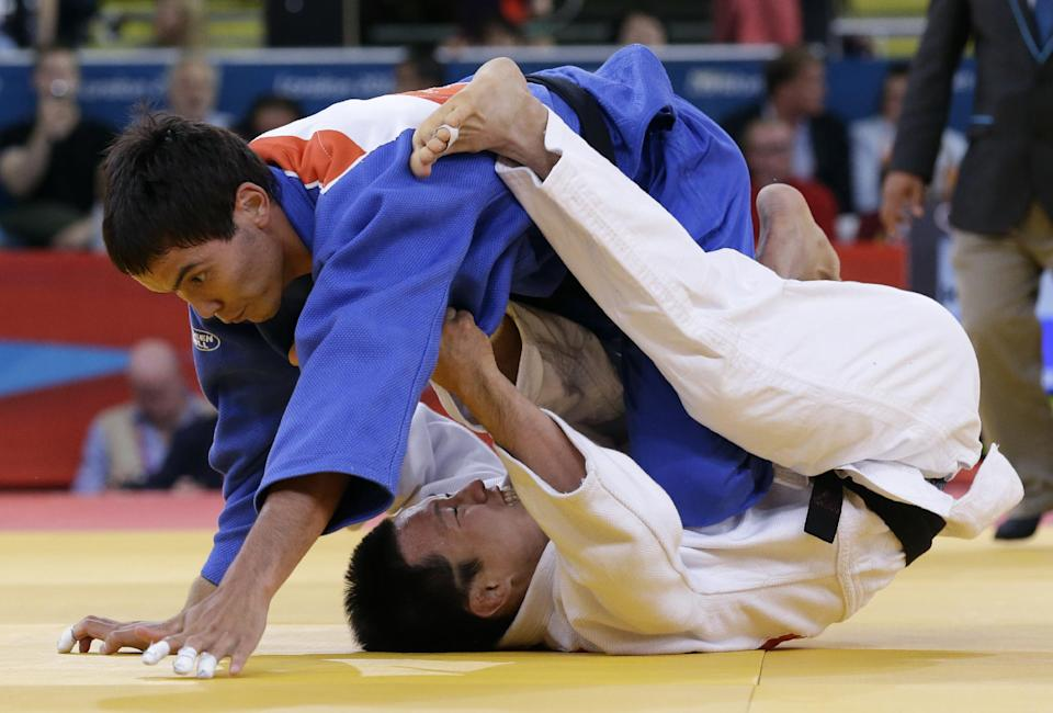Ki Chun Wang of South Korea competes with Rinat Ibragimov of Kazakhstan, top, during the men's 73-kg judo competition at the 2012 Summer Olympics, Monday, July 30, 2012, in London. (AP Photo/Paul Sancya)