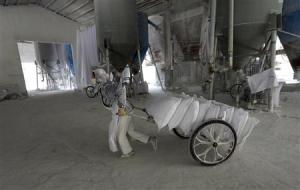 Worker wearing a mask pulls a cart loaded with limestone at a mill in Quzhou