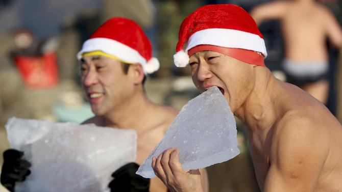A winter swimmer bites a piece of ice as he poses for photographs on a frozen lake at a park in Shenyang