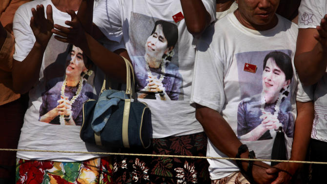 "In this photo taken, Sunday, Feb 26, 2012, supporters wearing T-shirts with the photographs of Myanmar's pro-democracy icon Aung San Suu Kyi printed on them, cheer during an election rally addressed by her in Thongwa village some 50 kilometers (31 miles) from Yangon, Myanmar. Suu Kyi's once-banished image now appears everywhere, on T-shirts, keychains and coffee mugs. Pirated copies of ""The Lady"", the big screen version of  Suu Kyi's life, are the best-selling DVD on Yangon streets. (AP Photo/Altaf Qadri)"