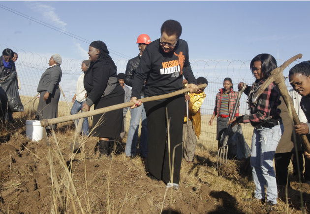 Graca Machel, center, the wife of former South African President Nelson Mandela works in the garden of a community center near Nelson Mandela house  in Qunu, South Africa,  Monday, July 18, 2011. Mill