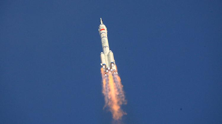 In this photo released by China's Xinhua News Agency, the Long March-2F carrier rocket carrying China's manned Shenzhou-9 spacecraft blasts off from the launch pad at the Jiuquan Satellite Launch Center in Jiuquan, northwest China's Gansu Province, Saturday, June 16, 2012. (AP Photo/Xinhua, Li Gang) NO SALES