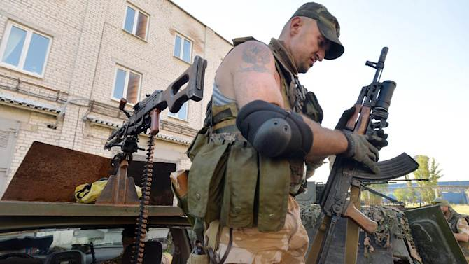A member of the pro-Ukraine Donbass Battalion checks an automaric rifle seized from pro-Russians, while patroling the outskirts of the eastern Ukrainian city of Lysychansk on July 26, 2014