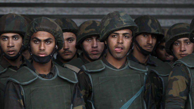 FILE - In this Tuesday, Dec. 11, 2012 file photo, Egyptian army soldiers stand guard during a demonstration in front of the presidential palace in Cairo, Egypt. Egypt's powerful military is showing signs of growing impatience with the country's Islamist leaders, criticizing their policies and issuing thinly-veiled threats that it might seize power again. The tension is raising the specter of another military intervention in politics much like the one in 2011, when generals ousted longtime authoritarian leader Hosni Mubarak to end the 18-day popular uprising.  (AP Photo/Petr David Josek)