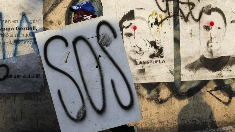 "An anti-government protester walks with a wooden board reading ""SOS"" during a protest in Caracas"