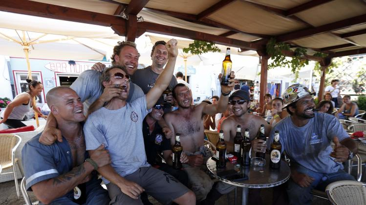 Dutch salvage workers celebrates after the refloat operation maneuvers that allowed cruise liner Costa Concordia to leave Giglio Island