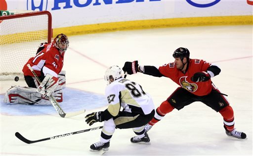 CORRECTS SPELLING TO SIDNEY- Ottawa Senators goaltender Craig Anderson (41) watches as Pittsburgh Penguins' Sidney Crosby (87) shoots the puck while Senators' Marc Methot (3) looks on during the first