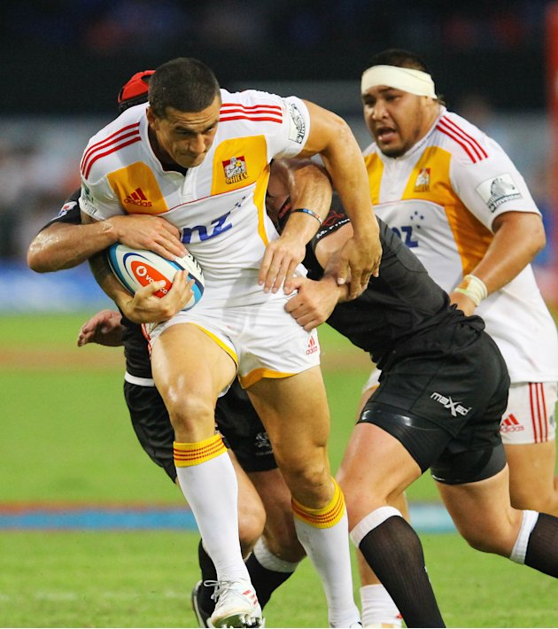 New Zealand Waikato Chiefs' Sonny Bill Williams (L) is tackled by Durban Sharks players during a Super 15 rugby union match at the Mr Price Kings Park Rugby Stadium on April 21, 2012.  AFP PHOTO  (Pho