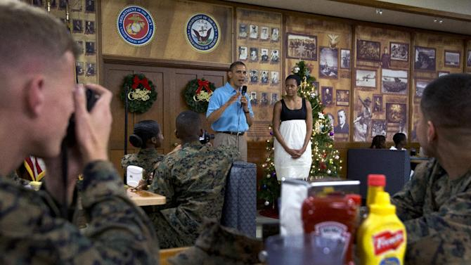 President Barack Obama speaks as first lady Michelle Obama listens during a visit with members of the military and their families in Anderson Hall at Marine Corp Base Hawaii, Tuesday, Dec. 25, 2012, in Kaneohe Bay, Hawaii. The first family is in Hawaii for a holiday vacation. (AP Photo/Carolyn Kaster)