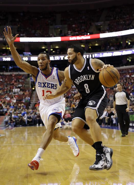 Brooklyn Nets' Deron Williams, right, dribbles past Philadelphia 76ers' Evan Turner during the first half of an NBA basketball game, Friday, Dec. 20, 2013, in Philadelphia