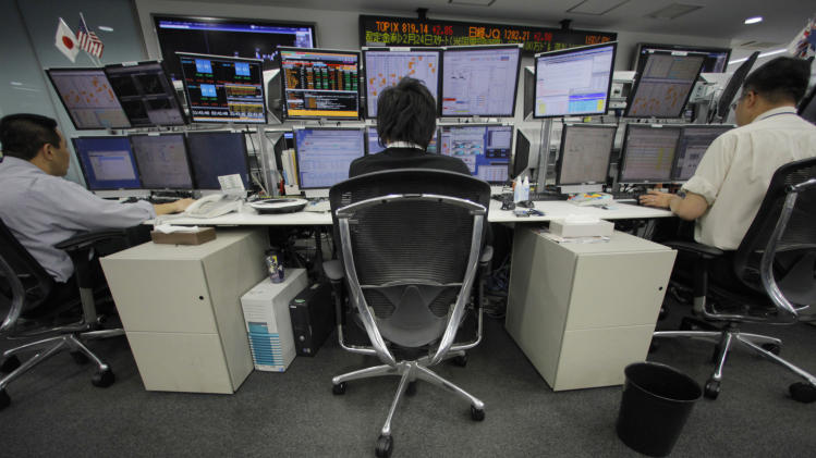 Money traders work at a foreign exchange firm in Tokyo Wednesday, Feb. 22, 2012. The U.S. dollar rose to the 80-yen mark Wednesday for the first time since Aug. 4 in midday Tokyo time. (AP Photo/Itsuo Inouye)