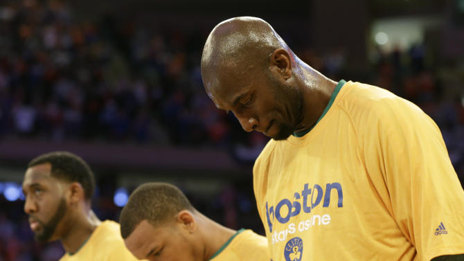 Boston Celtics center Kevin Garnett. right, and teammates bow their heads during a moment of silence for those injured and killed in the Boston Marathon bombings before the start of Game 1 of an NBA playoff basketball game against the New York Knicks at Madison Square Garden in New York, Saturday, April 20, 2013.  (AP Photo/Kathy Willens)
