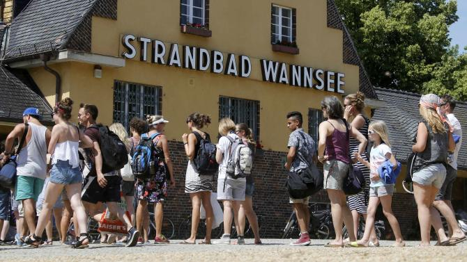 People queue during hot sunny summer day at the entrance of Berlin's Wannsee lido