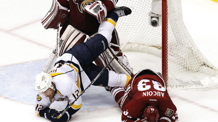 Nashville Predators' Mike Fisher (12) flips over Phoenix Coyotes' Adrian Aucoin (33) in the third period during Game 2 in an NHL hockey Stanley Cup Western Conference semifinal playoff series, Sunday, April 29, 2012, in Glendale, Ariz. The Coyotes won 5-3. (AP Photo/Ross D. Franklin)