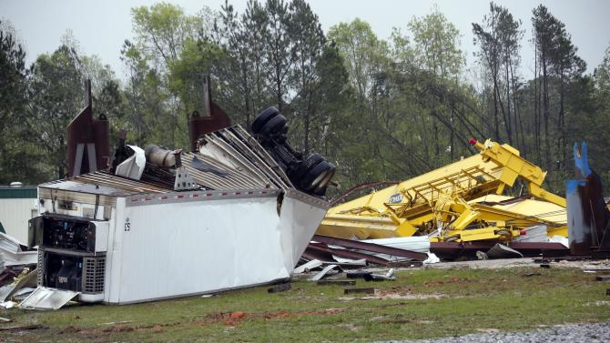 Wind twisted lifts and cranes and a trailer are among the debris that litter the grounds of Contract Fabricators Inc. in Kemper County, where authorities said one person died and another was injured when an apparent tornado hit Thursday, April 11, 2013 near De Kalb, Miss. Bent pieces of tin hung from the heavily damaged building and a tractor trailer was twisted and overturned. Debris from the business was strewn through the woods across the street. Sightseers drove slowly by the destruction, taking pictures. (AP Photo/Rogelio V. Solis)
