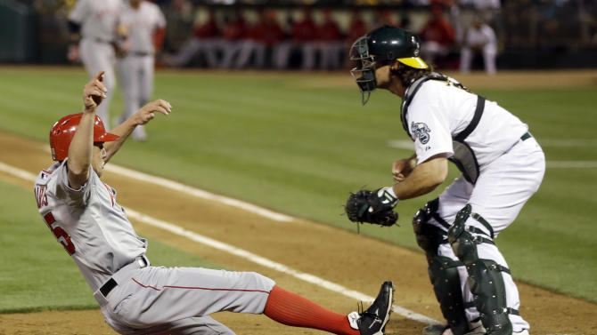 Los Angeles Angels' Peter Bourjos, left, scores past Oakland Athletics catcher John Jaso on a sacrifice fly ball from Los Angeles Angels' Josh Hamilton during the fifth inning of a baseball game on Monday, April 29, 2013 in Oakland. Calif. (AP Photo/Marcio Jose Sanchez)