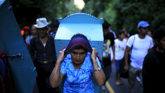 "A woman carries the statue of Saint Christopher during a pilgrimage of Catholic devotees known as ""Cumpas"" in the town of Cuishnahuat, El Salvador"