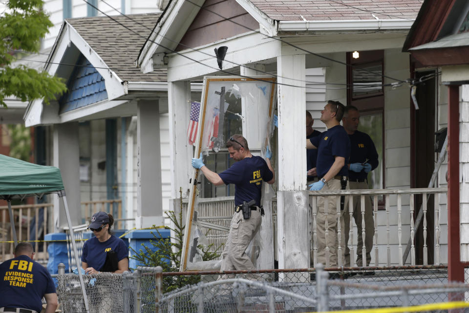 FILE - In this Tuesday, May 7, 2013 file photo, members of the FBI evidence response team carry out the front screen door from the house where three women were held captive, in Cleveland. Cleveland officials are trying to keep the house intact until the trial of the women's suspected abductor is concluded. (AP Photo/Tony Dejak, File)