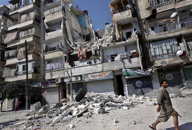 FILE - In this Friday, Aug. 17, 2012 file photo, a Syrian man walks by a building destroyed in an airstrike in Aleppo, Syria. The growing use of air power by the Syrian regime is causing a spike in civilian casualties, according to activists. Its forces stretched thin on multiple fronts, President Bashar Assad's regime has significantly increased its use of air power against Syrian rebels in recent weeks, causing mounting civilian casualties. The shift is providing useful clues about the capability of the air force as Western powers consider the option of enforcing a no-fly zone over the northern part of the country.(AP Photo/Khalil Hamra, File)