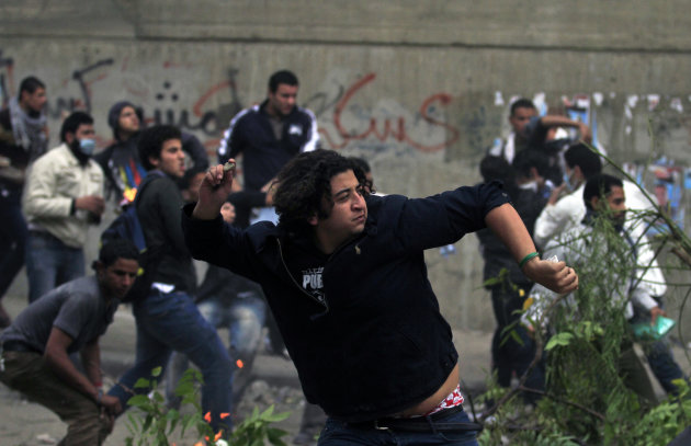 Protesters throw stones at Egyptian riot police during clashes near the interior ministry in downtown cairo, Egypt, Sunday, Nov. 20, 2011. Firing tear gas and rubber bullets, Egyptian riot police on Sunday clashed for a second day with thousands of rock-throwing protesters demanding that the ruling military quickly announce a date to hand over power to an elected government. The police battled an estimated 5,000 protesters in and around central Cairo's Tahrir Square, birthplace of the 18-day uprising that toppled authoritarian leader Hosni Mubarak in February. (AP Photo/Khalil Hamra)