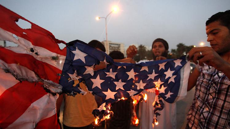 "FILE - In this Friday, Sept. 14, 2012, photo, Libyan followers of Ansar al-Shariah Brigades burn the U.S. flag during a protest in front of the Tibesti Hotel, in Benghazi, Libya, as part of widespread anger across the Muslim world about a film ridiculing Islam's Prophet Muhammad. Ansar al-Shariah is among the most powerful of the heavily armed militias that the government relies on to keep security in Benghazi. Suspicion in last week's deadly attack that killed the American ambassador to Libya has focused on members of a hardcore Islamist militia known for its sympathies to al-Qaida, its fierce animosity to the U.S. and its intimidation of Muslims who don't conform to its strident ideology. Around 150 members of Ansar al-Shariah Brigades chanted "" Obama, Obama, we are all Osama."" (AP Photo / Mohammad Hannon, File)"