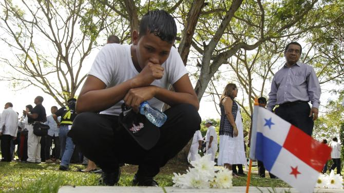 Family member of a victim of the invasion of Panama reacts by a grave at the Jardin de Paz cemetery, in remembrance of the 25th anniversary of the U.S invasion of Panama, in Panama City