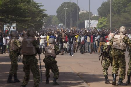 Soldiers attempt to stop anti-government protesters from entering the parliament building in Ouagadougou