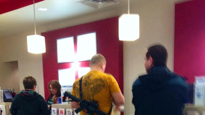 This cell phone photo provided by Cindy Yorgason shows a JC Penney shopper with an assault rifle over his shoulder in Riverdale, Utah, Wednesday, Jan. 16, 2013.  Cindy Yorgason said she was trying to exchange an item at the store when she spotted the man and took his photo.  The man, identified as 22-year-old Joseph Kelley, says he wanted to demonstrate that the weapons aren't dangerous when handled by law-abiding citizens.  Kelley told The Salt Lake Tribune the rifle was an unloaded AR-15, and he was also carrying a loaded Glock 19c on his hip.   (AP Photo/Cindy Yorgason))