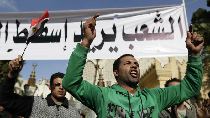 """Egyptian protesters chant anti-Muslim Brotherhood and Egyptian President Mohammed Mosri slogans outside the presidential palace under a banner with a defaced picture of President Mohammed Morsi and Arabic that reads """"the people want to bring down the regime,"""" at the protests site, in Cairo, Egypt, Saturday, Dec. 8, 2012. Egypt's military has warned of 'disastrous consequences' if the political crisis gripping the country is not resolved through dialogue. (AP Photo/Hassan Ammar)"""