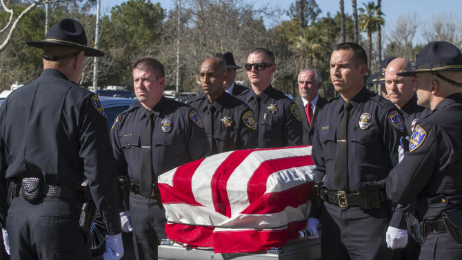FILE - This Feb. 13, 2013 file photo shows Riverside Police officers carrying the casket of fellow officer Michael Crain during his burial ceremony at the Riverside National Cemetery in Riverside, Calif. The 34-year-old Crain was ambushed in his patrol car on Feb. 7. Authorities believe the shooter was ex-Los Angeles policeman Christopher Dorner. (AP Photo/Damian Dovarganes, File)
