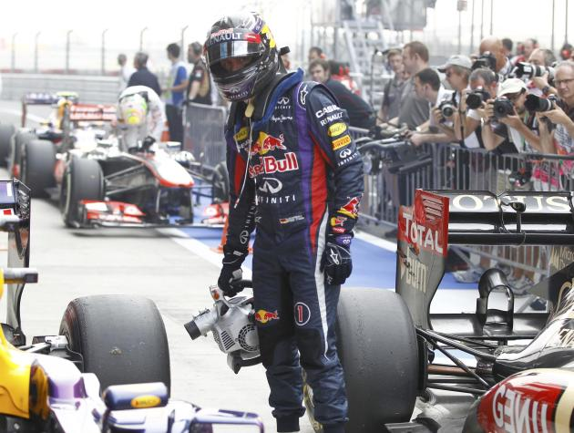 Red Bull Formula One driver Vettel uses a fan after the qualifying session of the Indian F1 Grand Prix at the Buddh International Circuit in Greater Noida