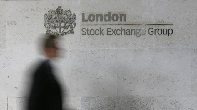 A man walks past the London Stock Exchange in the City of London