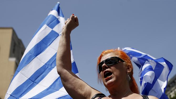 A woman with Greek national flags behind her gestures during a demonstration in support of Greece, in Madrid