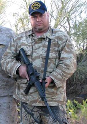 """FILE - This undated file photo provided in 2010 by Jason """"JT"""" Ready, shows Ready posing with an assault rifle. Police have identified Ready on Thursday, May 3, 2012, as one of the five people killed in a shooting in a Phoenix suburb on Wednesday. (AP Photo/Courtesy Jason """"JT"""" Ready, File)"""